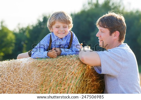 Young father and his little son having fun on yellow hay field in summer. Happy family of two. Active outdoors leisure with children on warm summer day. - stock photo