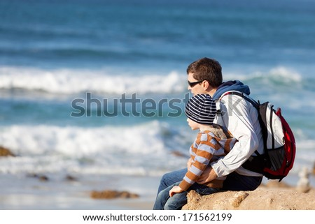 young father and his little son sitting together at the beach - stock photo