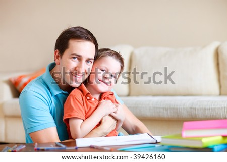 Young father and his son drawing and reading together - stock photo