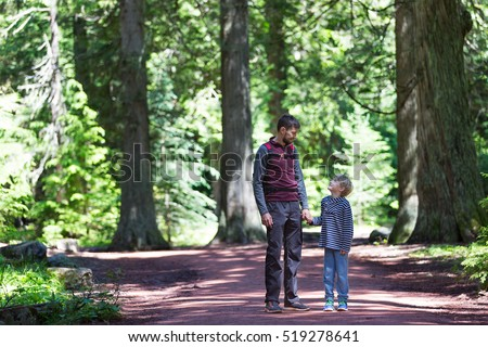 young father and his son enjoying hike together in forest in glacier national park, montana