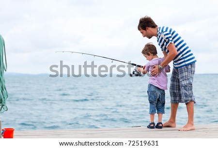 Young father and his son fishing together from wooden jetty - stock photo