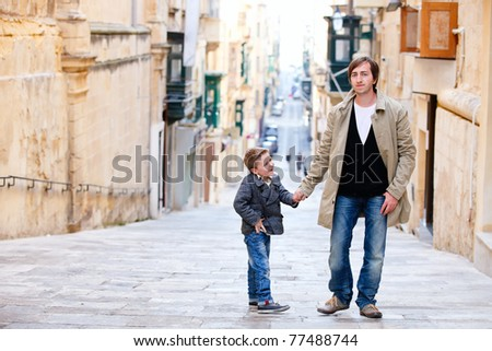 Young father and his son outdoors in city - stock photo