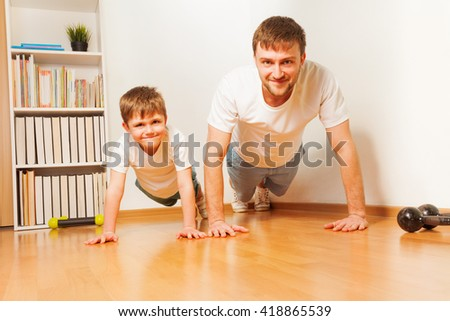 Young father and his son pushing up at the room - stock photo