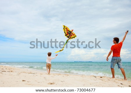 Young father and his son running with kite on the beach - stock photo