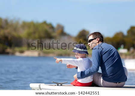 young father and his son sitting at the marina dock and spending fun time together; adorable little boy pointing with his finger and showing something to his father - stock photo