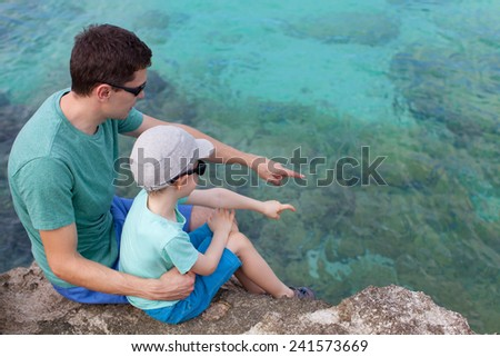 young father and his son sitting at the rocky beach and exploring underwater life - stock photo