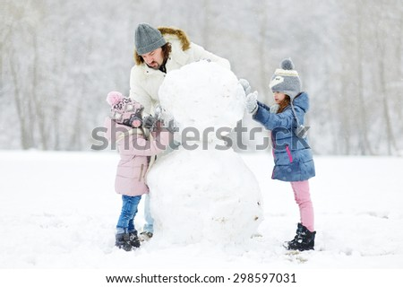 Young father and his two daughters building a snowman on winter day - stock photo