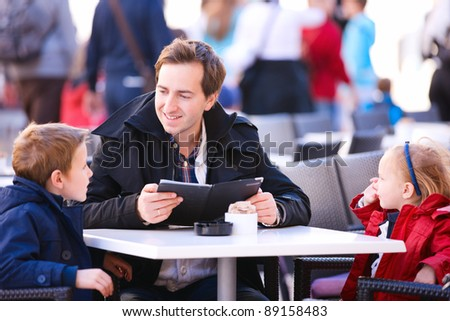 Young father and his two kids at outdoor cafe on autumn day - stock photo