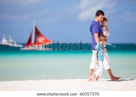 Young father and his two kids walking along tropical beach