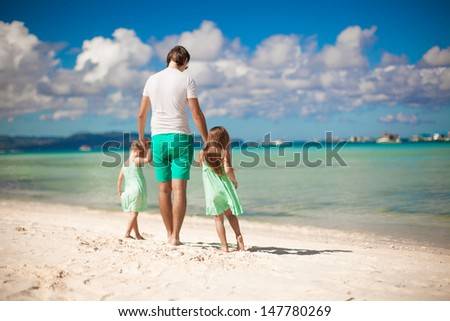 Young father and his two little kids walking by the sea - stock photo