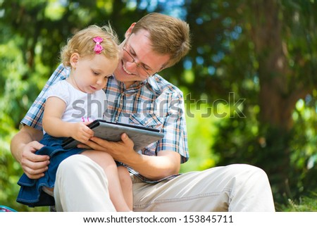 Young father and little  cute daughter having fun in summer park - stock photo
