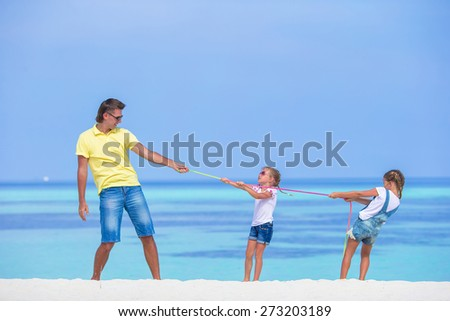 Young father and little girls have fun together during tropical vacation - stock photo