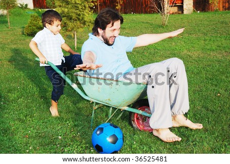 Young father and little son are playing outdoor - stock photo