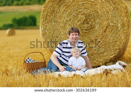 Young father and little son, kid boy having picnic on yellow hay field in summer, outdoors. Family having fun together. - stock photo