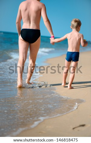 Young father and little son walking at ocean beach. Rear view - stock photo