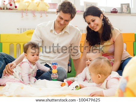 Young father and mother playing with children at home - stock photo