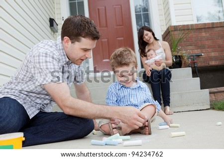 Young Father And Son Drawing With Chalk And Mother Sitting With Baby in Background. - stock photo