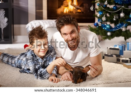 Young father and son lying on floor, playing with puppy received for christmas. - stock photo