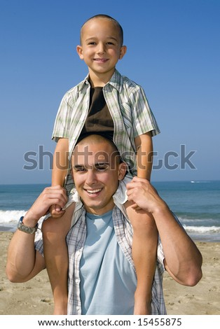 Young father and son on the beach - stock photo
