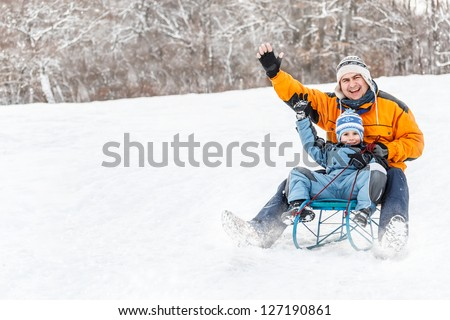 Young father and son sledding at winter time - stock photo