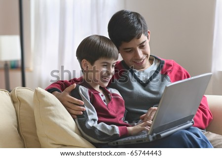 Young father and son using laptop - stock photo
