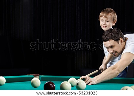 Young father and the son play billiards - stock photo