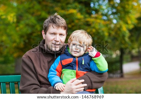 Young father and toddler boy sitting on bench in autumn park - stock photo