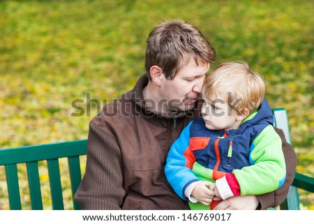 Young father and toddler boy sitting on bench in autumn park