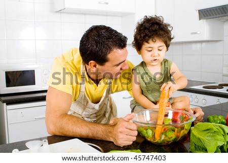 young father and toddler son playing in modern kitchen - stock photo