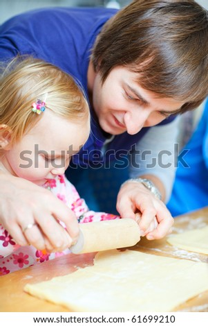 Young father baking together with his little daughter - stock photo
