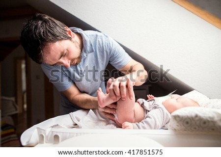 Young father changing diaper to his little baby son - stock photo