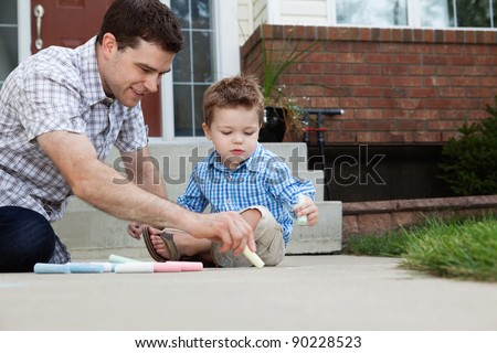 Young father drawing with chalk on the ground with son sitting beside