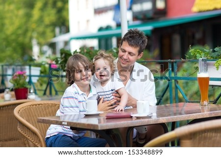 Young father enjoying a meal with his son and baby daughter in an outside cafe on a nice summer day - stock photo