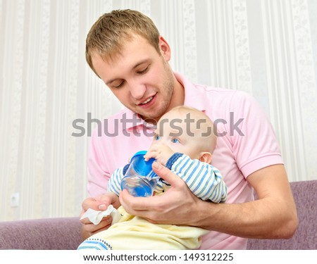 young father feeding baby - stock photo