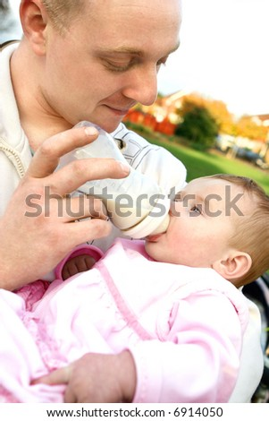 Young father feeding milk to his tired baby girl, outdoor - stock photo