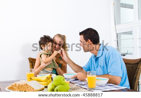 young father feeding toddler boy breakfast - stock photo