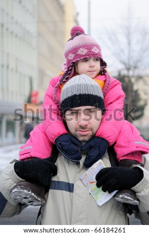 Young father gives his daughter a ride on his back