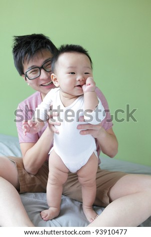 Young Father Happy Play with His Baby (an asian family) with green home background - stock photo