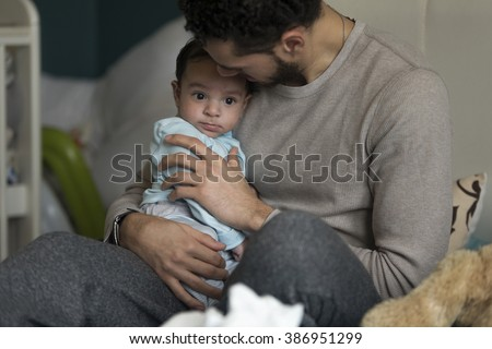 Young father having cuddles with his baby. They are sitting on dad's bed. - stock photo