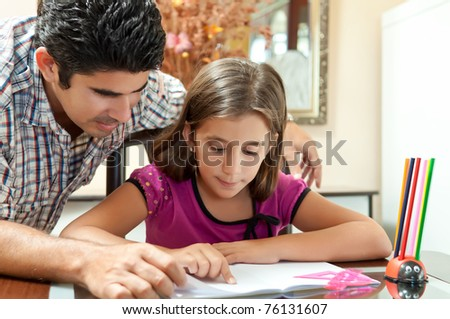 Young father helping her daughter with her school project at home - stock photo