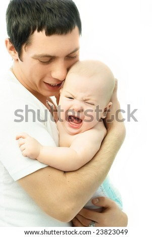 young father holding a crying baby in his arms and talking ot him - stock photo