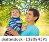 Young father holding a pretty little boy in nature - stock photo