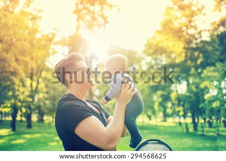 Young father holding delicate newborn infant in arms outdoor in park. Happy parenting concept, father's day and family - stock photo