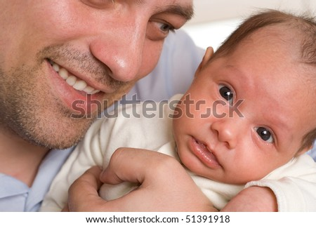 young father holding hands on newborn daughter