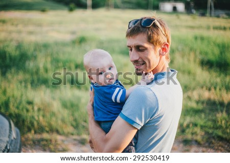 Young father holding his baby son on hands outdoors - stock photo
