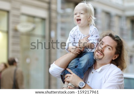 Young father holding his little girl outdoors - stock photo