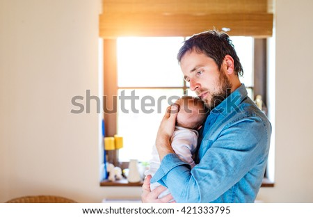 Young father holding his newborn baby son in his arm. Young father is enjoying time with his child. Father and son at home. Handsome father with little boy. Happy fathers day.