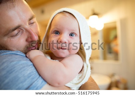 Young father holding his son wrapped in towel after bathing him