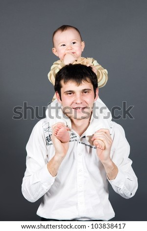 Young father holding little son on his shoulders