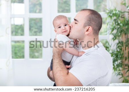 Young Father hugging and kissing his little son - stock photo